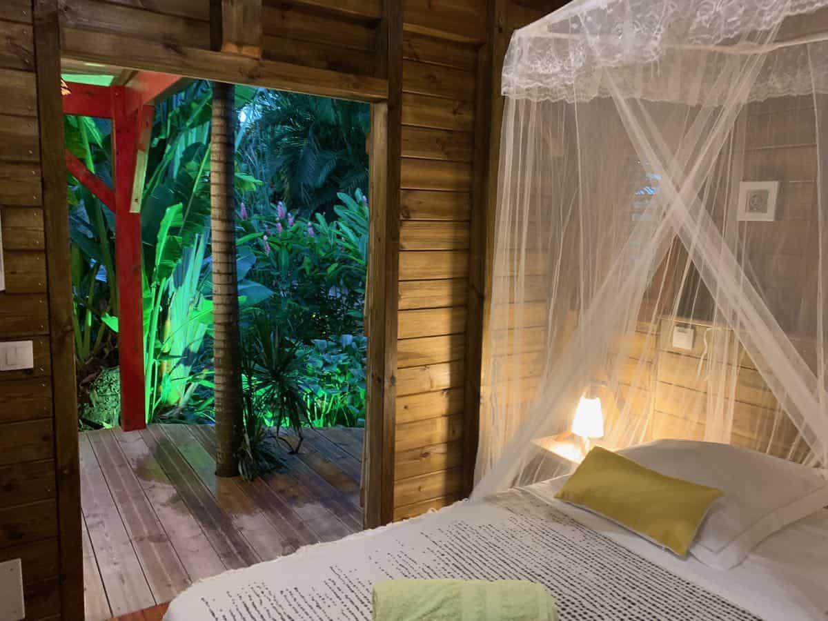 Un lit douillet, dans un bungalow confortable situé au coeur d'un jardin tropical.